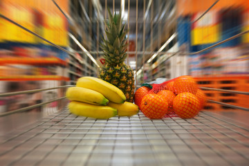 Shopping cart with fruits moving through supermarket