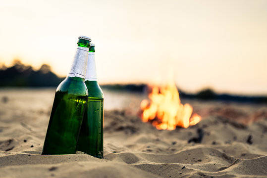 Close-up of two green beer bottles on sand in front of campfire at beach