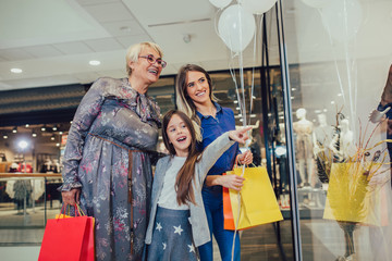 Mother, adult daughter and granddaughter in shopping mall together