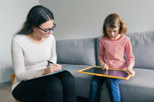 Professional child psychologist talking with child girl in office, child draws a drawing