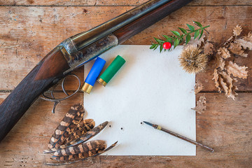 Self adhesive Wall Murals Hunting Beautiful hunting season still life/vintage hunting rifle, cartridges, vintage pen on the target with traces of bullets, pheasant feathers on old wooden background