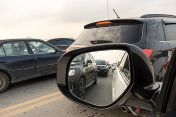 Reflection of traffic flow in left side rear view mirror at rush hour