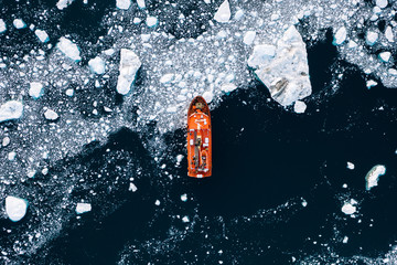 Minimalistic aerial view of an orange icebreaker in sea ice
