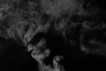 White smoke on a black background. Texture of smoke. Clubs of white smoke on a dark background for an overlay