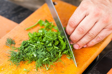 Greens chopping. Cook hand with knife