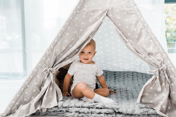 smiling adorable toddler sitting in baby wigwam