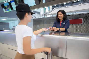 Young woman in international airport at check-in counter, giving passport to an officer reception and waiting for her boarding pass.