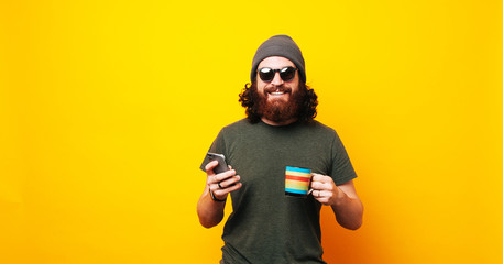 Happy bearded hipster man using phone and holding cup of coffee