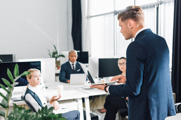 serious young businessman using laptop and looking at colleagues in office