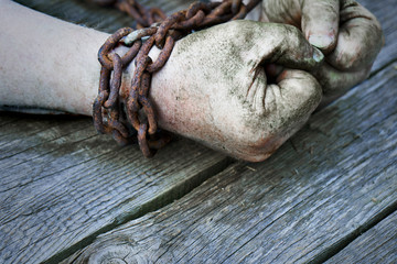 Powerful dirty male hands clenched into fists chained with rusty chain.