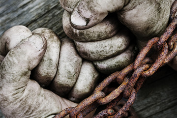 Powerful dirty male hands clenched into fists chained with rusty chain. Wall mural