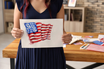 Woman holding watercolor painting of American national flag, closeup