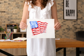 Woman holding watercolor painting of American national flag