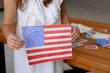 Woman holding drawing of American national flag, closeup