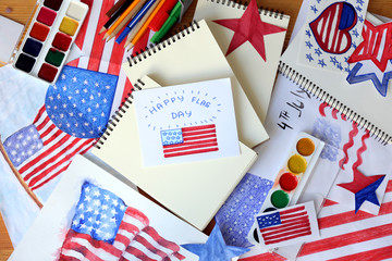 Many paintings of American national flag with paints and pencils on wooden table