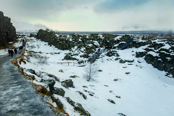 Þingvellir National Park, on a cold, wintry day, with people walking the pathway.