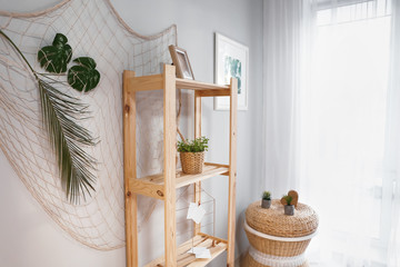 Shelving unit with green plant and decor in room