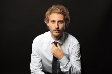 Portrait of young businessman on black background