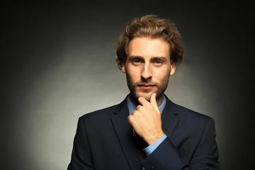 Portrait of young handsome businessman on black background