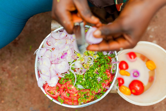 close up of african woman mincing vegetables in africa village preparing food