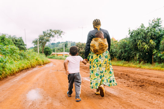 african mother and two children walk alone in red clay road in  village as a family in traditional dress