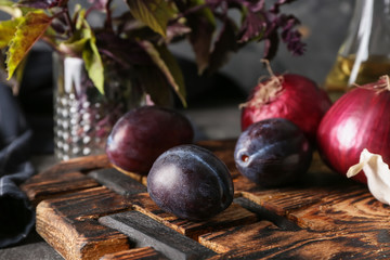 Fresh plums with vegetables on wooden board