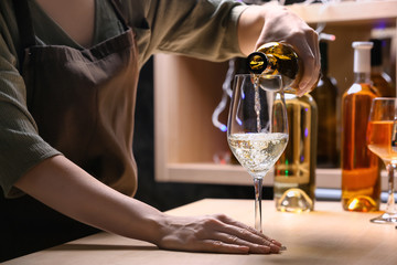 Female barman pouring wine from bottle into glass on counter