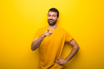 Man on isolated vibrant yellow color points finger at you with a confident expression Wall mural
