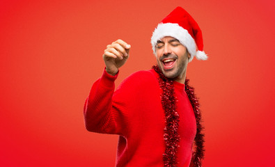Man with red clothes celebrating the Christmas holidays enjoy dancing while listening to music at a party on red background