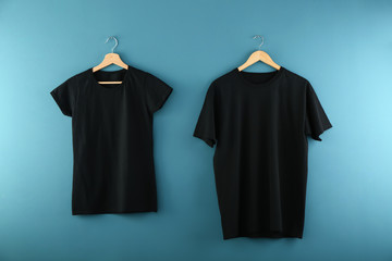 Hangers with blank black t-shirts on color background