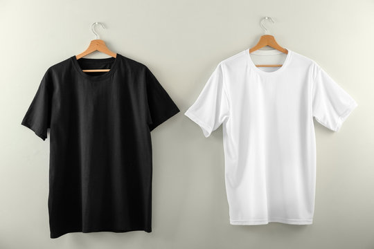 Hangers with blank t-shirts on light background