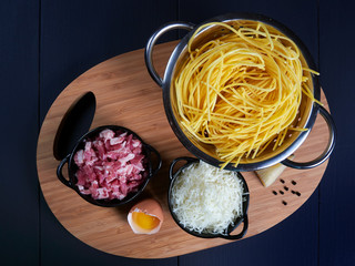 Ingredients for spaghetti carbonara: fresh spaghetti, grated pecorino romano, bacon (or guanciale), egg yolk, black peppercorns, top view