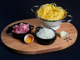 Ingredients for spaghetti carbonara: fresh spaghetti, grated pecorino romano, bacon (or guanciale), egg yolk, black peppercorns