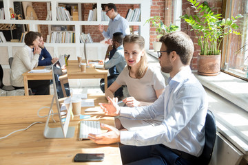 Diverse millennial colleagues work at computer, discuss project or business idea, female trainer or coach help male employee with pc, man and woman talk cooperating at shared table in coworking space