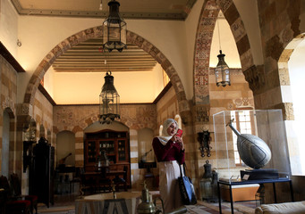 A woman takes a picture with her cell phone in the Debbane Museum in Sidon