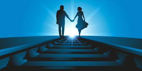 Un couple d'amoureux se promène, main dans la main, le long d'une voix ferrée en direction de l'horizon face au soleil.