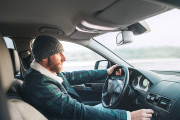 Warm dressed Bearded Man driving a new modern auto. Inside car view.