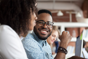 Close up of smiling African American employee look at female colleague chatting in office, happy black male worker talk with woman coworker, having casual conversation at workplace, have fun Wall mural