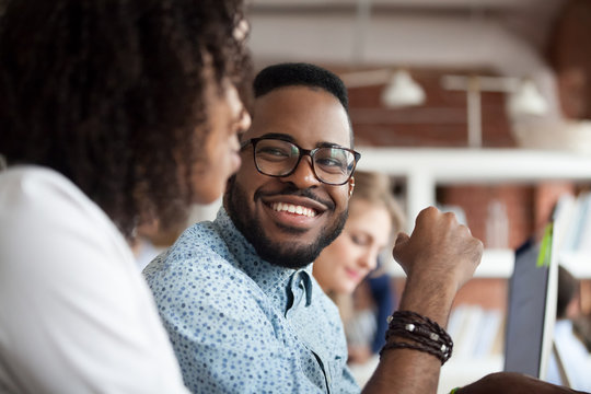 Close up of smiling African American employee look at female colleague chatting in office, happy black male worker talk with woman coworker, having casual conversation at workplace, have fun