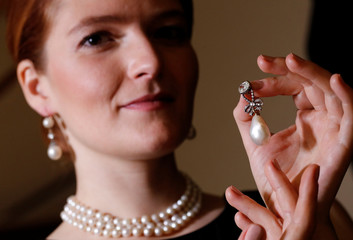 A model holds a natural pearl and diamond pendant once owned by Marie Antoinette together with wearing a pair of natural drops and a necklace featuring 119 natural pearls in Geneva