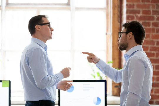 Mad male colleagues have disagreement in office arguing on work issues, furious millennial employee point at coworker blaming for mistake or failure, businessman accuse partner disputing at workplace