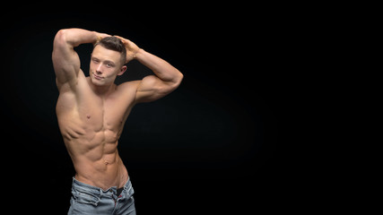 Muscular shirtless man isolated on dark background.