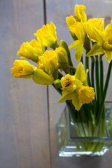Bouquet of yellow narcissus in the glass on the wooden background