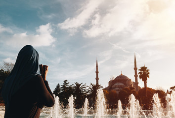 Young Muslim Woman photographing Blue mosque with fountain in the foreground. - istanbul