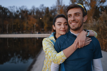 Happy sporty couple portrait outdoors while hugging