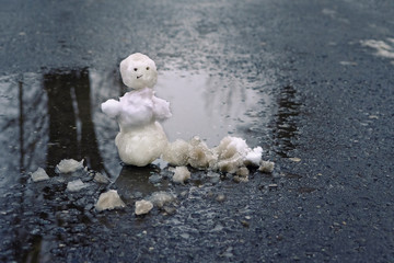 melted snowman in  puddle. bad warm rainy winter weather.