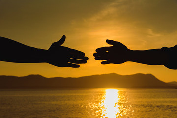 Silhouette of helping hand concept and international day of peace, Expression of Business Collaboration, Help hand, Teamwork concept, Business handshake ideas.