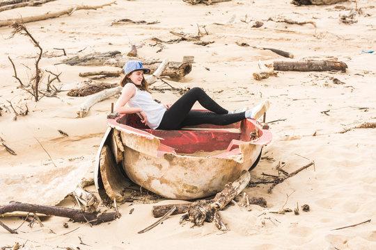 Side view of teenage girl sitting on broken boat