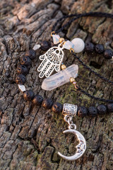 Fashionable bracelets with lava stone and pendants on wooden background