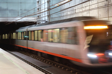 A motion blur photo of the Bilbao metro on rails getting to the Guggenheim Museum stop during an autumn cloudy day, in Basque Country, Spain